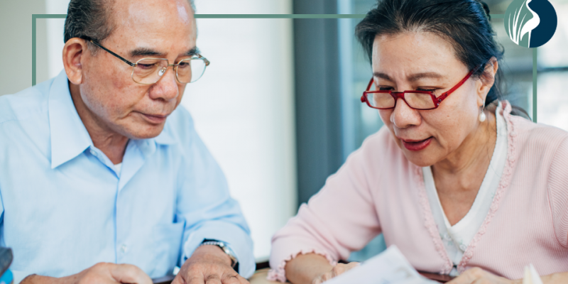 Senior couple reviewing financial documents with south shore retirement services logo