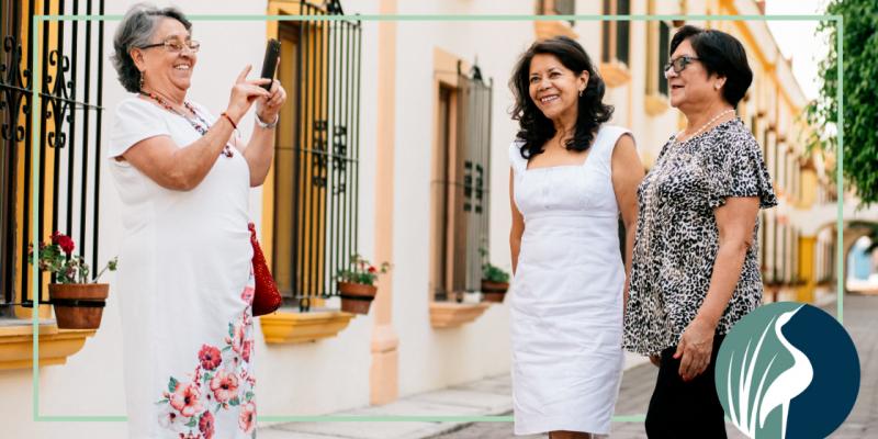 Three senior women taking photos while traveling